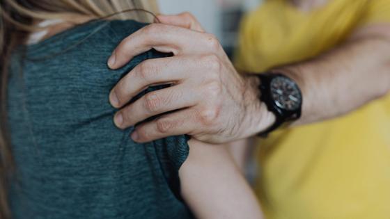 Мужчина берет за плечо женщину