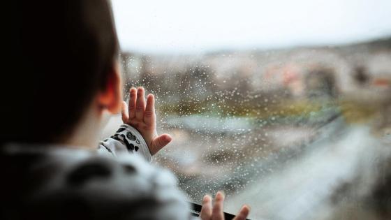 Ребенок касается окна рукой