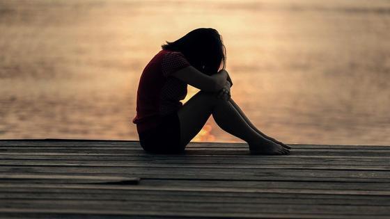 Девушка сидит на берегу