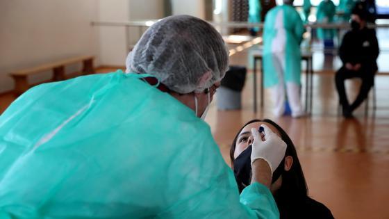 Медик берет биоматериал для ПЦР-теста
