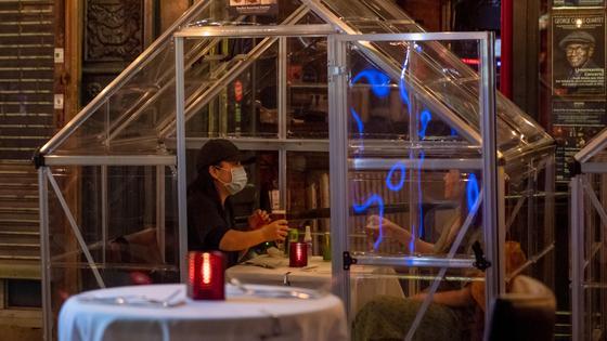 женщина в маске сидит в стеклянном домике в ресторане
