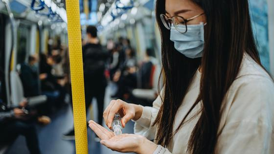 Девушка наносит на руки антисептик в вагоне метро