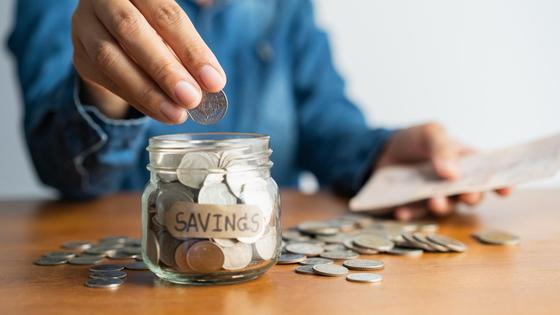 Женщина кладет монетку в банку с деньгами