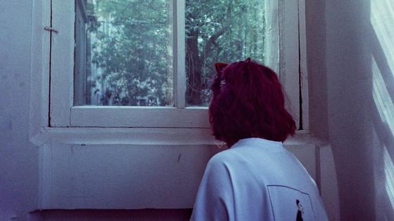 Девочка стоит возле окна
