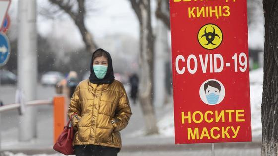 Девушка в маске идет по тротуару