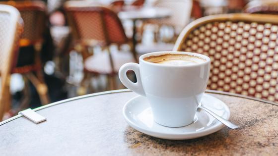 Чашечка кофе с блюдцем стоит на столике