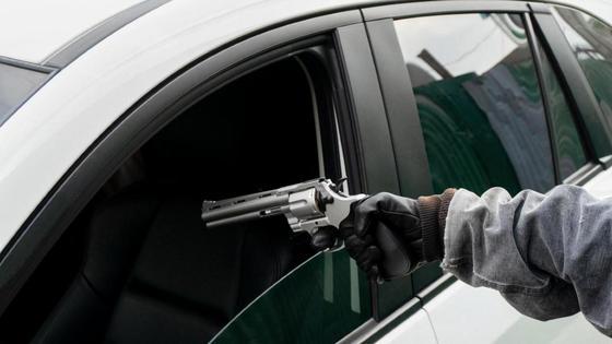 Мужчина целится пистолетом в сиденье водителя