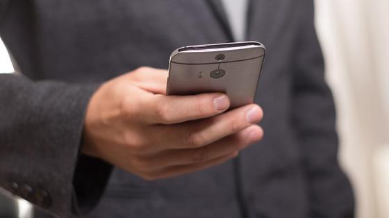 Мужчина в костюме держит телефон в руке