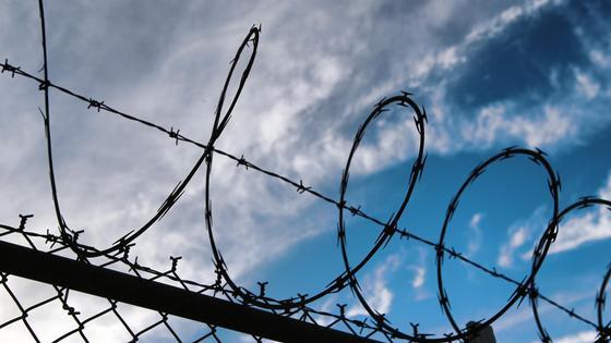 Колючая проволока натянута над забором