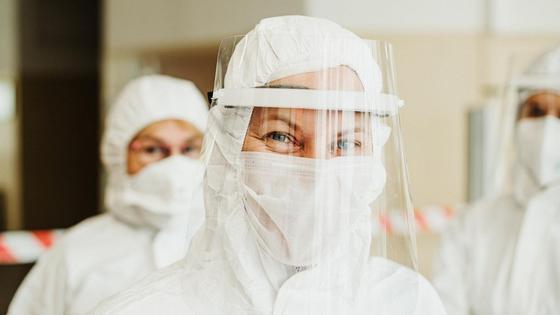 медики стоят в защитных костюмах