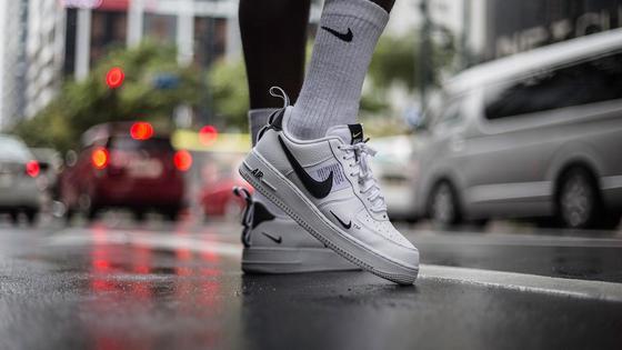 Ноги в белых кроссовках и носках на мокром асфальте