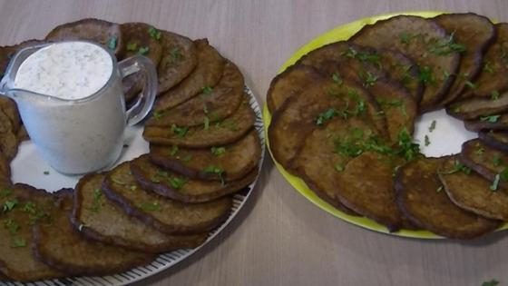 Котлеты из куриной печени на тарелках с соусом и зеленью