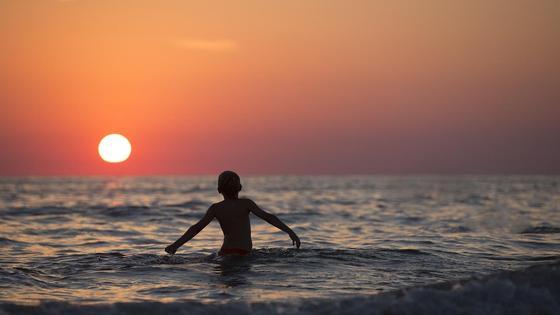 Мальчик в реке смотрит на закат