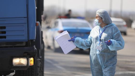 медик в защитном костюме стоит возле грузовика
