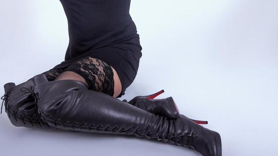 Девушка в кожаных сапогах сидит на полу
