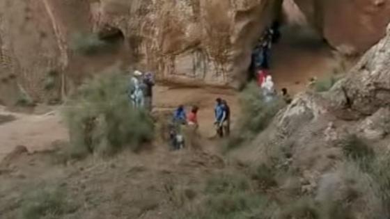Несколько людей стоят у селевого потока