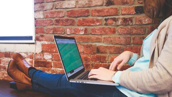 Девушка сидит с ноутбуком на ногах
