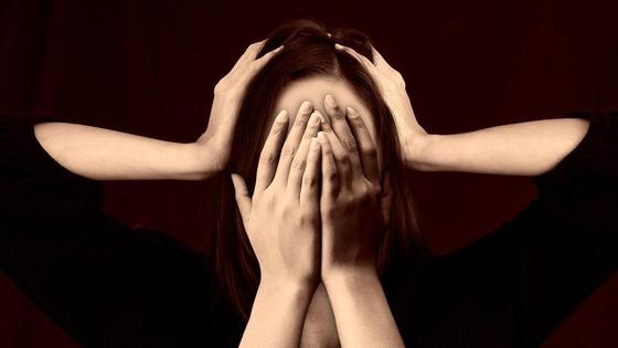 Руки закрывают лицо девушки и сжимают ее голову