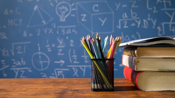Стакан с карандашами и три книги на фоне доски в классе