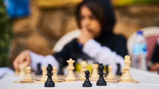 Молодой парень сидит возле шахматной доски