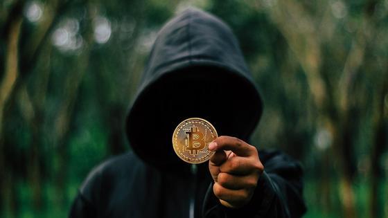 Мужчина в капюшоне держит монету с изображением логотипа биткоина