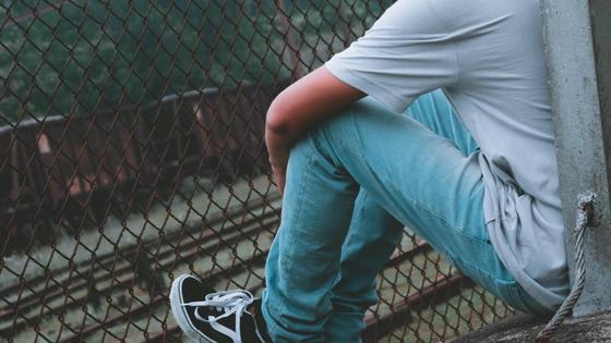 Подросток сидит на улице