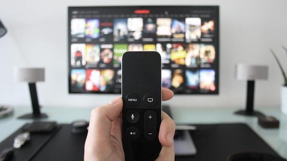 Мужчина держит в руках пульт от телевизора