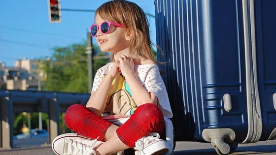 Девочка в очках сидит на асфальте