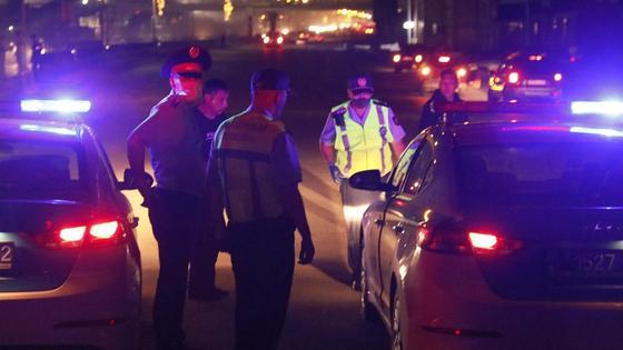 Полицейские и автомобили стоят на дороге