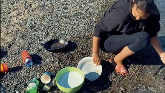 Аиша моет посуду в море