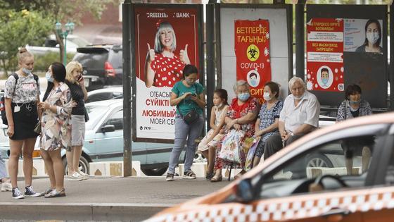 Люди стоят на остановке в Алматы