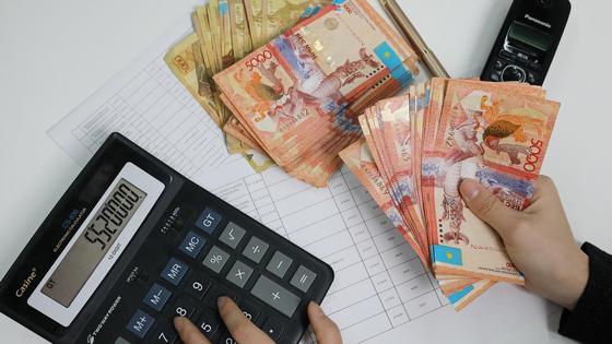 человек считает деньги на калькуляторе
