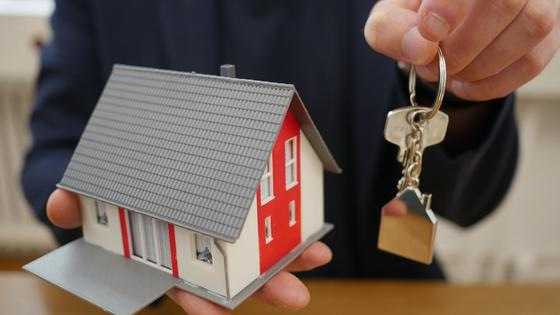 Мужчина держит игрушечный домик и ключи