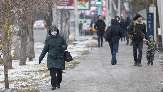 Женщина в маске идет по зимнему городу