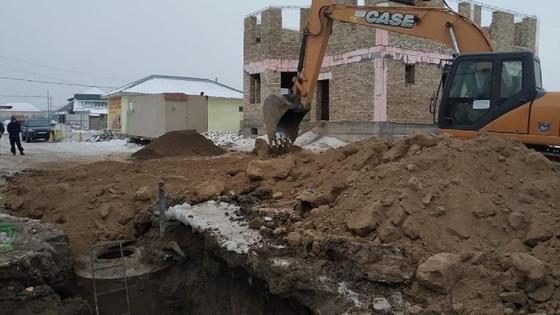 Экскаватор засыпает землей яму