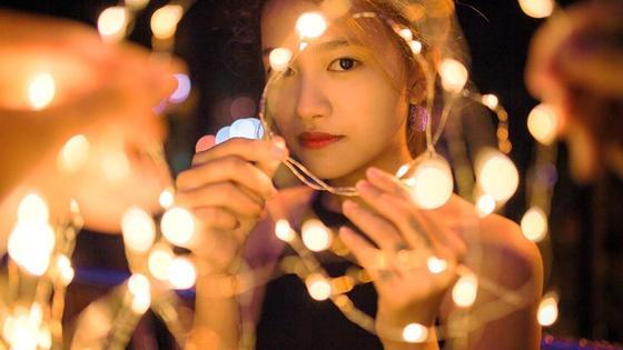 девушка держит в руках гирлянду фонариков