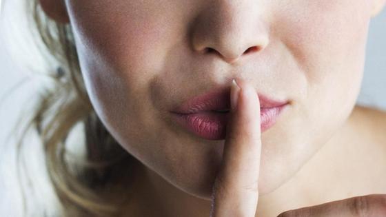 девушка держит палец у губ