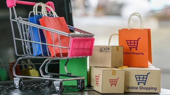 Миниатюрные пакеты, посылки и тележка для покупок выставлены на ноутбуке