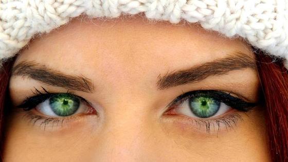 Красивые зеленые глаза девушки в белой шапке