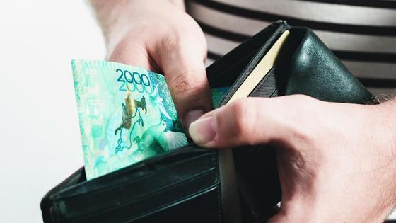 Мужчина держит в руках кошелек с одно купюрой в 2000 тенге