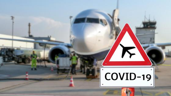 "Знак с надписью ""COVID-19"" на фоне самолета"