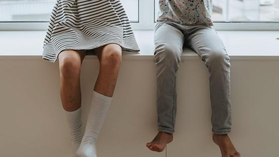 Девочка и мальчик сидят на подоконнике