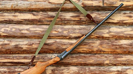 Ружье висит на стене на крючке