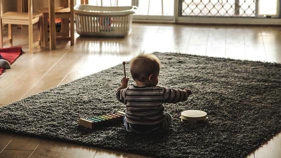 Ребенок играет сидя на полу