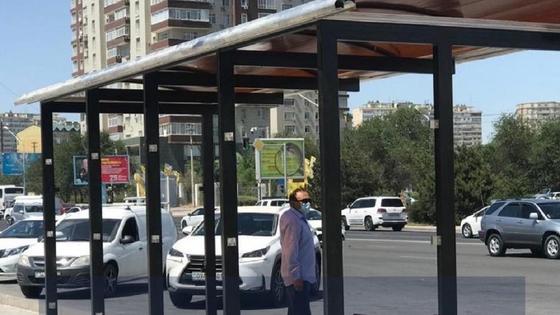 Мужчина стоит на остановке в Актау
