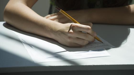 Человек сидит за столом и пишет карандашом на бумаге