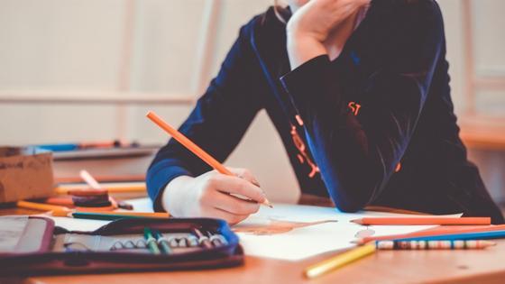 Школьница рисует карандашами