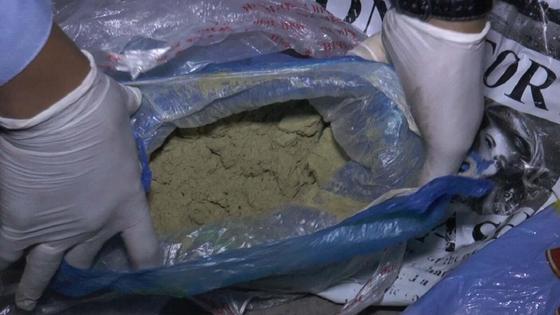 Полицейский показывает изъятые наркотики