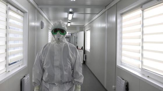 Медработник стоит в коридоре инфекционной больницы
