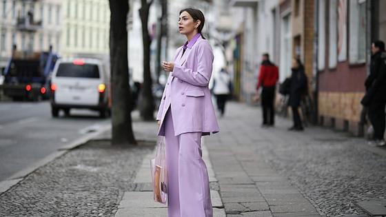 Девушка в лиловом костюме стоит на улице